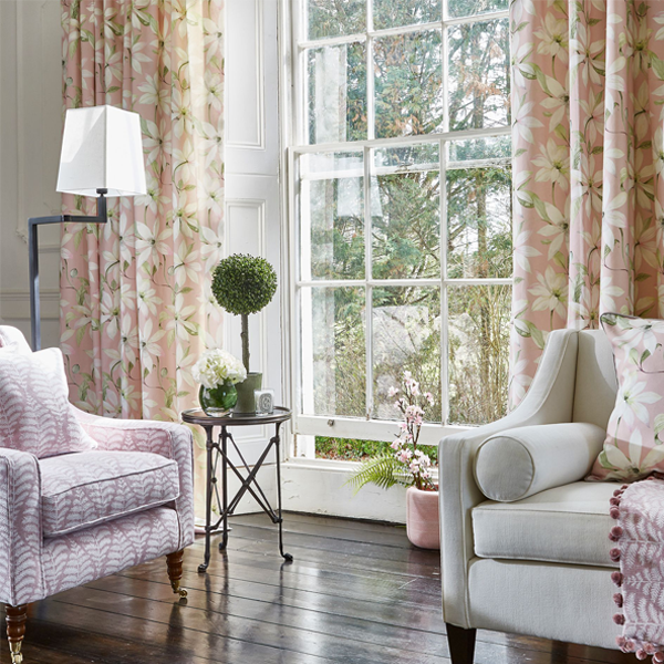 flowery pink curtains in room with two arm chairs